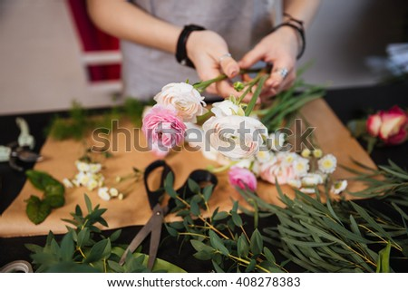 Closeup of hands of young woman florist creating bouquet of pink roses on the table #408278383