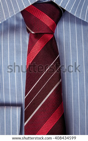 Luxury blue shirt with ornament with red striped tie. Business suit macro shot #408434599