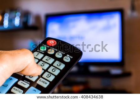 Hand hold the remote control to change channels on Tv #408434638