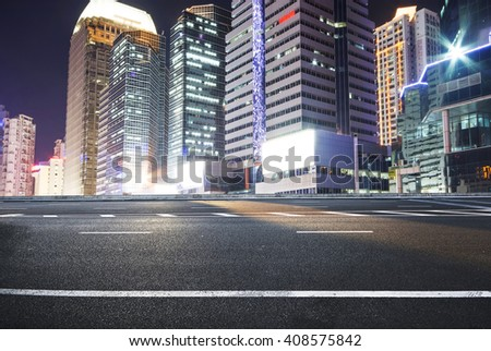 Asphalt road and a city with illuminated buildings on the horizon #408575842