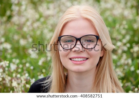 Blonde girl with glasses in the field surrounded by flowers #408582751