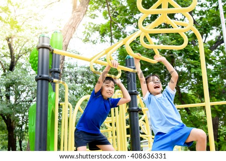 Young asian boy hang the yellow bar by his hand to exercise at out door playground under the big tree. #408636331