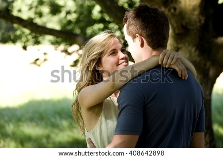 A young couple standing beneath a tree, embracing #408642898