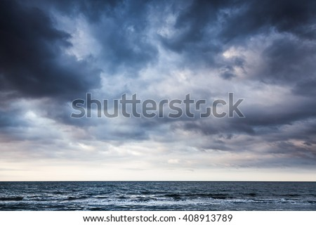 Dramatic stormy dark cloudy sky over sea, natural photo background #408913789