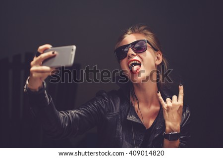 Young cute girl l hipster,sitting at cafe holding a smart phone,answering texts,calls,letters,posts photos in instagram,outdoor portrait,close up,elaborated and bracelets on the hands make selfie