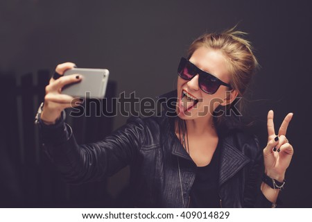 Young cute female l hipster,sitting at cafe holding a smart phone,answering texts,calls,letters,posts photos in instagram,outdoor portrait,close up,elaborated and bracelets on the hands make selfie