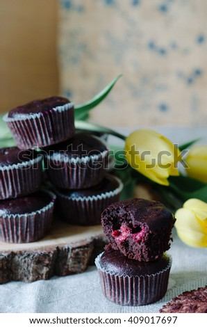 Chocolate muffins with a cherry on the table with yellow tulips #409017697