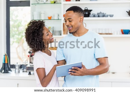 Happy couple using digital tablet at home #409098991