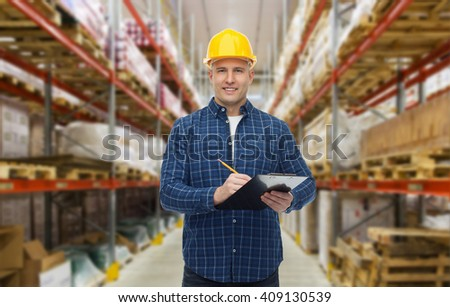 wholesale, logistic, business, export and people concept - happy man or manager in helmet with clipboard and pencil checking goods over warehouse background #409130539