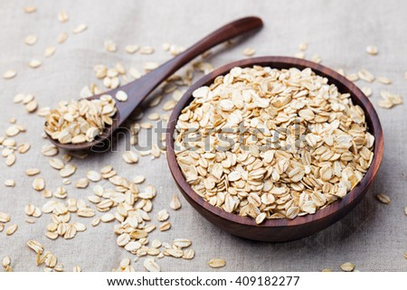 Healthy breakfast Organic oat flakes in a wooden bowl Grey textile background Copy space #409182277