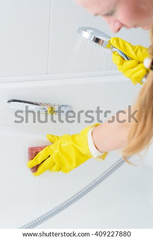 A woman cleaning bath at home. Female washing bathtub in yellow gloves #409227880
