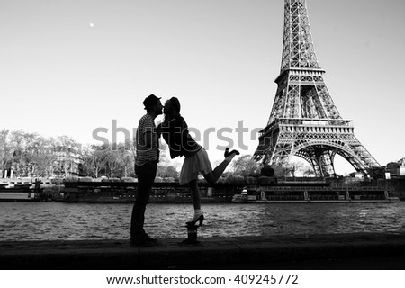 Kissing couple silhouettes under the Eiffel Tower in black and white #409245772