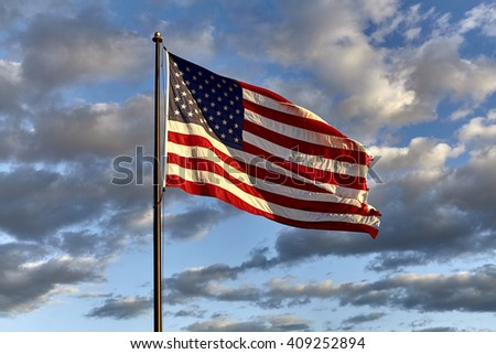 American flag on flagpole waving in the wind against clouds, blue sky and the moon #409252894