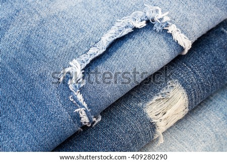 Destroyed torn ripped denim blue jeans with patch, close up, Flat Lay #409280290