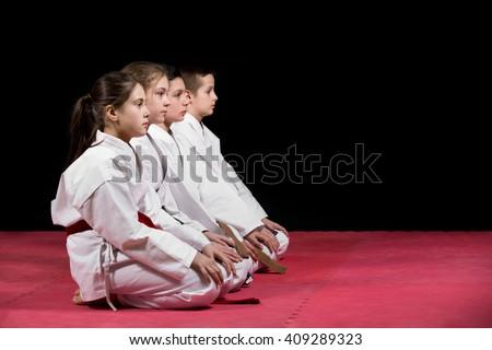 Children in kimono sitting on tatami on martial arts seminar. Selective focus. Royalty-Free Stock Photo #409289323