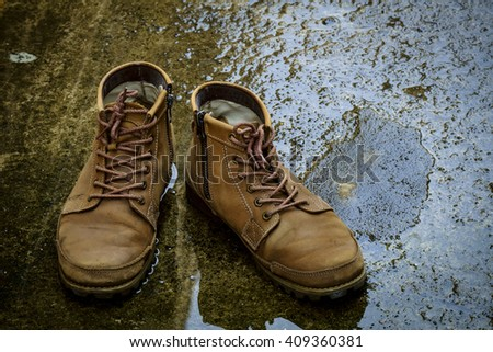 Men leather shoes on a concrete floor after rain Royalty-Free Stock Photo #409360381
