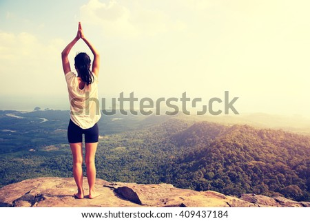 young woman practice yoga at mountain peak cliff #409437184