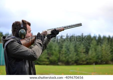 man shooting shotguns at clay pigeon outdoors #409670656
