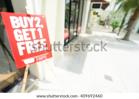 Blurred photo of Buy 2 get 1 free red sign in front of store