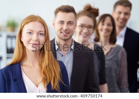 Attractive young businesswoman posing with her team of co-workers in a receding line behind her looking at the camera with a confident smile #409750174