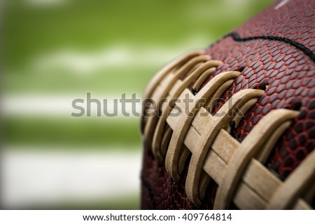 Macro of a vintage worn american football ball with visible laces, stitches and pigskin pattern