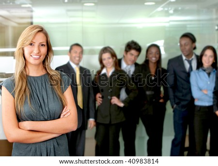 Business woman smiling in an office with her team behind her #40983814