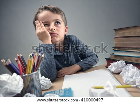 Thinking child bored, frustrated and fed up doing his homework Royalty-Free Stock Photo #410000497