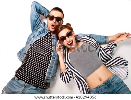 fashion couple in sunglasses lies on a white background, smiling happily and surprised. Vogue Style #410294356