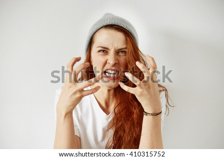 Close up isolated portrait of young annoyed angry woman holding hands in furious gesture. Young female with red hair in white T-shirt and cap. Negative human emotions, face expressions. Film effect  Royalty-Free Stock Photo #410315752