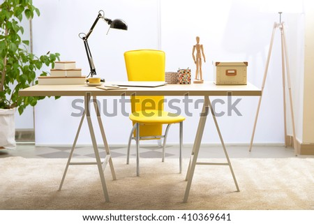 Workplace with table, yellow chair and laptop in living room #410369641