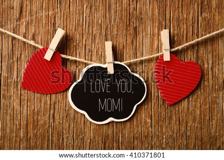 the text I love you mom written in a chalkboard in the shape of a thought bubble hanging in a rope with a wooden clothespin next to some red hearts, against a rustic wooden background #410371801