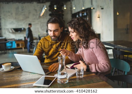 Young hipster male and female working with laptop together in trendy cafe #410428162