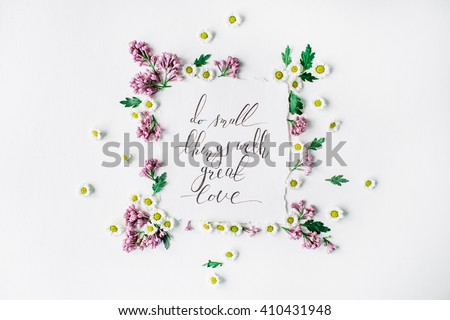"""inspirational quote """"Do small things with great love"""" written in calligraphy style on paper with wreath frame with lilac and chamomile isolated on white background. flat lay, overhead view, top view"""