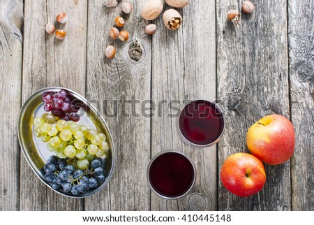 autumn still life with wine, apples, grapes, nuts on old wooden #410445148