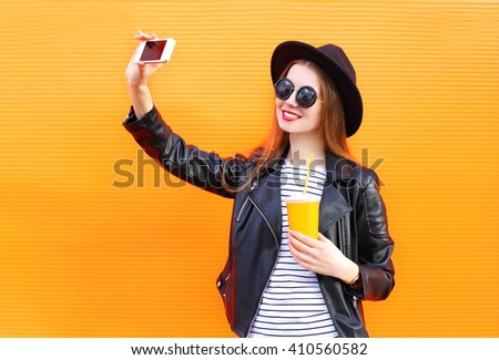 Fashion pretty smiling woman makes self portrait on smartphone in black rock style over city orange background