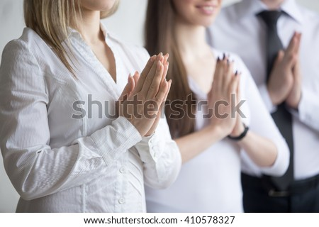 Business and healthy lifestyle concept. Close-up of young office workers standing in yoga pose at workplace. Smiling business people relaxing with arms folded in Prayer gesture on break time #410578327
