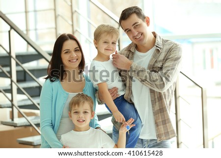 Happy family with key in new house on stairs background #410615428