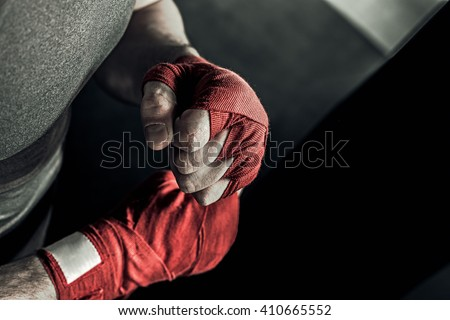 Closeup male hand of boxer with red boxing bandages. Fists of fighter before the fight or training in sport gym. Royalty-Free Stock Photo #410665552
