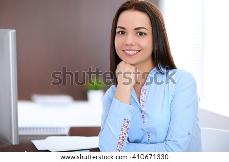 Young business woman sitting and writing at the table  in office #410671330