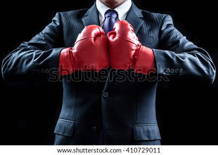 Businessman , boxing gloves , fighting pose Royalty-Free Stock Photo #410729011