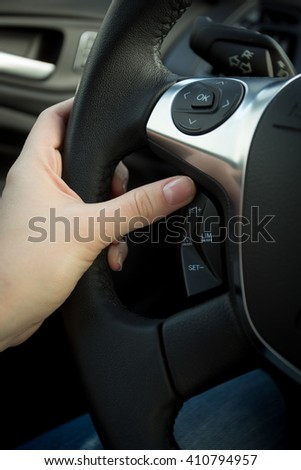 Closeup photo of female driver adjusting cruise control system on steering wheel #410794957