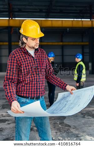 Construction Worker In Safety Helmet reading blueprints #410816764