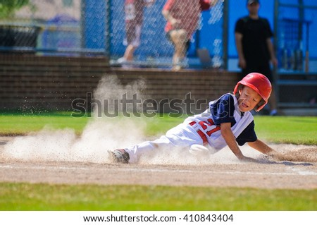 Youth baseball player sliding in at home.