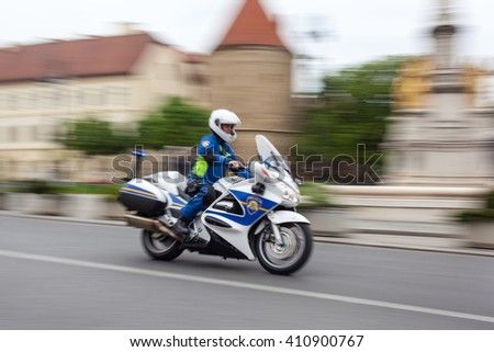 ZAGREB, CROATIA - APRIL 24, 2016: - International cycling race Tour of Croatia 2016. - Stage 6. Policeman on motorcycle passing by cathedral. #410900767