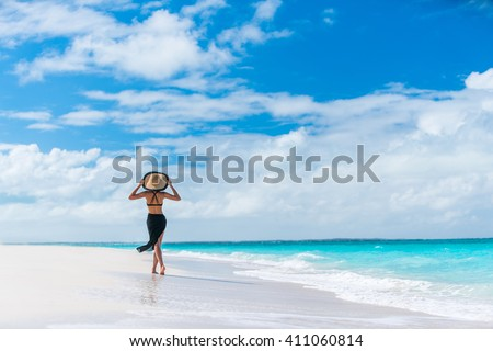 Luxury travel woman in black beachwear sarong walking taking a stroll on perfect white sand Caribbean beach. Girl tourist on summer holiday holding sun hat at vacation resort. Tropical landscape. #411060814
