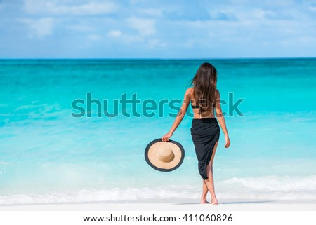 Woman in black bikini and sarong standing on beach. Elegant sexy female is wearing black bikini and sarong on beach. Woman is holding sunhat enjoying her summer vacation at resort in the Caribbean. #411060826