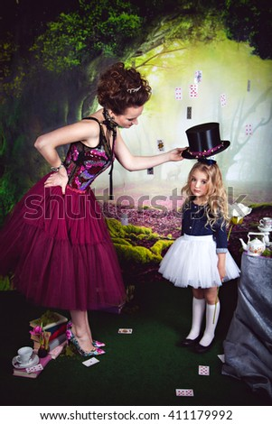 Evil Queen holding hat over little Alice