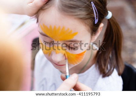 Child animator, artist's hand draws face painting to little girl. Child with funny face painting. Painter makes tiger eyes at girl's face. Children holiday, event, bithday party, entertainment.