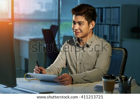 Smiling designer  drawing on tablet and looking at computer screen #411213721