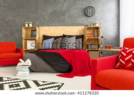 Spacious bedrooom in grey with stylish, red details #411278320